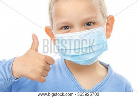 Little Boy In Medical Mask Shows Thumb Up On White Isolated Background. Healthcare  Concept. Prevent