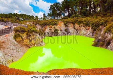 Devil's Bath with bright green water. The unique geothermal area of Rotorua. Volcanic Valley Waimangu, Wai-O-Tapu. New Zealand, North Island. Extreme, exotic and photo tourism concept