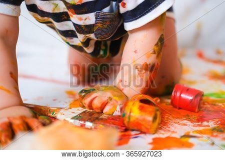 Cropped Cheerful Grimy Baby Crawls On The Floor Playing With Paint. Dirty Kid Close Up. Happy Leasur