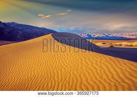 USA. Easily accessible dunes are located along Road 190. Magical desert morning. Mesquite Flat Sand Dunes - dunes in Death Valley. The sand lies in light waves. The concept of photo tourism