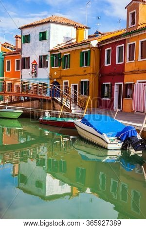 Island of Burano near Venice. Bright colored houses and tilt tower are reflected in the water of the canals. Boats are parked along the banks. The concept of cultural, historical and photo tourism
