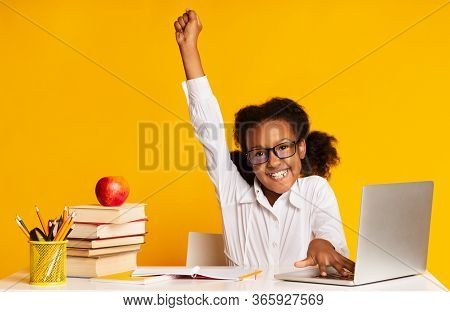 Online Classes. Happy African Schoolgirl At Laptop Raising Hand During Distant Lesson Learning From