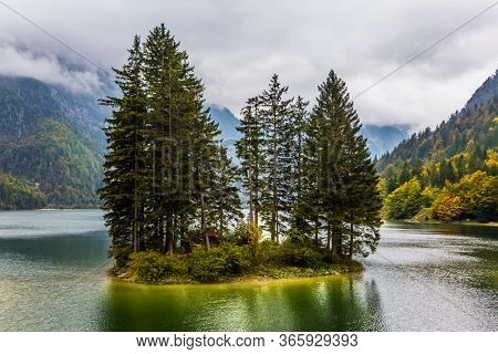 Alpine lake Di Predil in the fog. Small island in the middle of the lake is overgrown with pine trees. Among the pines there is a red tourist tent. The concept of mountain  and photo tourism