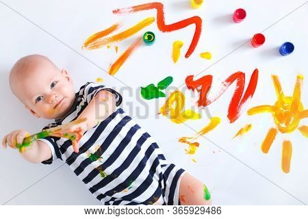 Top View Happy Cheerful Dirty Baby Playing With Paint And Brush On White Background. Happy Leasure A