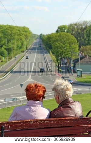 Two Elderly Women Talking While Sitting On Bench And Looking To The Highway. Old Girlfriends Are Res