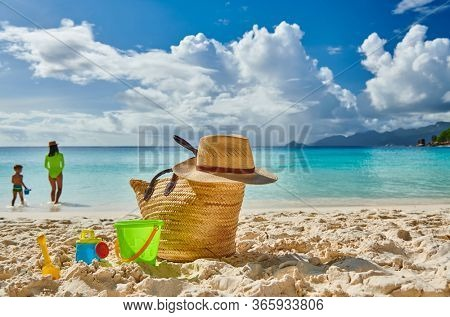 Three year old toddler boy on beach with mother. Beach bag and toys. Summer family vacation at Mahe, Seychelles.
