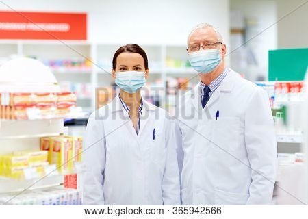 medicine, healthcare and technology concept - happy smiling apothecaries wearing face protective medical mask for protection from virus disease at pharmacy