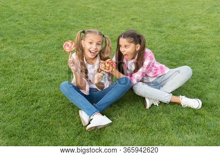 Happy Children Hold Candy Sit Grass. Sugar And Calories. Joyful Cheerful Friends Eating Sweets Outdo