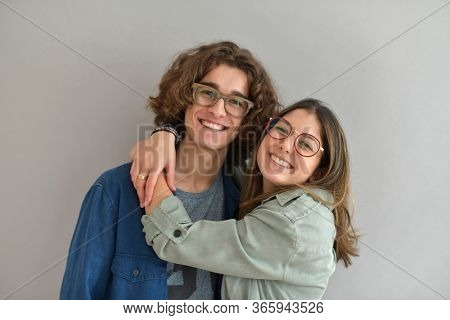 Young couple with eyeglasses standing on grey background, isolated