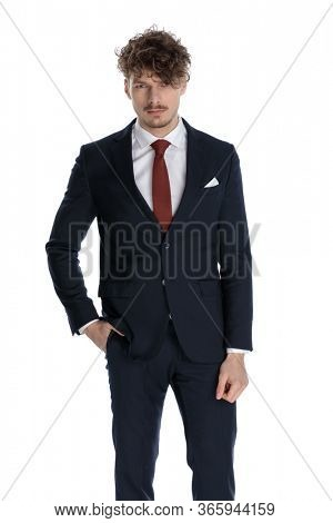 Bothered businessman frowning with hand in pocket while wearing suit and standing on white studio background