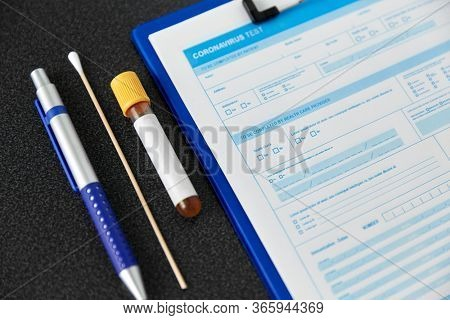 medicine, healthcare and pandemic concept - medical report on clipboard, beaker with test, cotton swab and pen on table