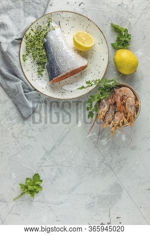 Trout Fish  Surrounded Parsley, Lemon, Shrimp, Prawn In Ceramic Plate. Light Gray Concrete Table Sur