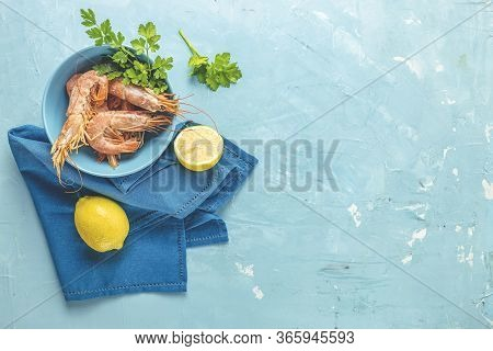 Shrimp, Prawn With Parsley In Blue Ceramic Plate Surrounded Napkin And Lemon On Light Classic Blue C