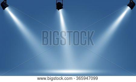 Spotlights illuminate empty stage blue background.