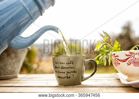 Concept Of Breakfast And Teatime In Open Air. Tea From Vintage Teapot, Pour Into Mug (inscription On