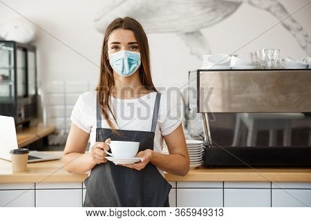 Business Owner Concept - Beautiful Caucasian Barista In Face Mask Offers Hot Coffee At The Modern Co