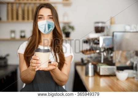 Business Owner Concept - Beautiful Caucasian Barista In Face Mask Offers Disposable Take Away Hot Co