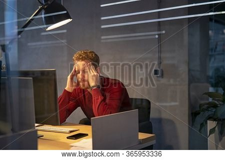 Upset businessman at desk with terrible headache. Tired business man working late in office. Young stressed man feeling headache after hard working for long hours on computer, overwork and burnout.