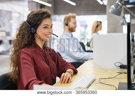 Desk consultant talking on hands-free phone. Smiling call center operator with headset working on support hotline. Busy call center agents working in a modern office, offering customer care service.