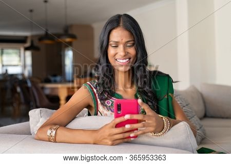 Smiling indian girl in traditional sari using smartphone at home. Young woman in ethnic wear sending phone message with smartphone. Beautiful hindu woman with bindi using app on mobile phone.