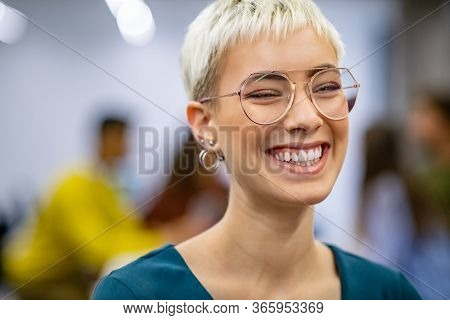 Successful business woman in modern office enjoying. Close up face of creative stylish woman smiling and looking at camera. Portrait of trendy university student laughing with classmates working.