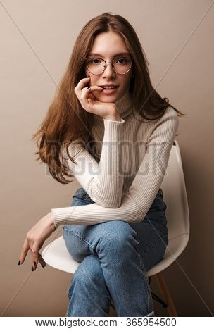 Photo of charming confident woman in eyeglasses looking at camera and sitting on chair isolated over grey wall