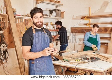 Young man as carpenter apprentice or trainee with tablet computer in workshop