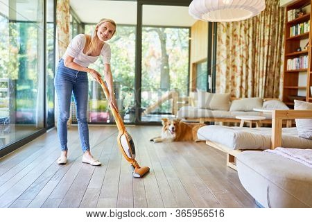 Housewife cleans the parquet floor in the living room with the vacuum cleaner