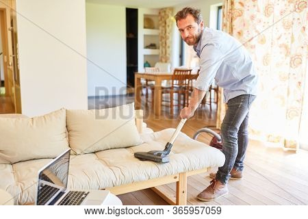 Man as a houseman with vacuum cleaner while vacuuming on a couch