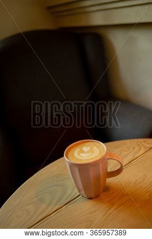 A Cup Of Hot Cappuccino Coffee On Wooden Table. Cappuccino With Latte Art In A Beautiful Cup On The