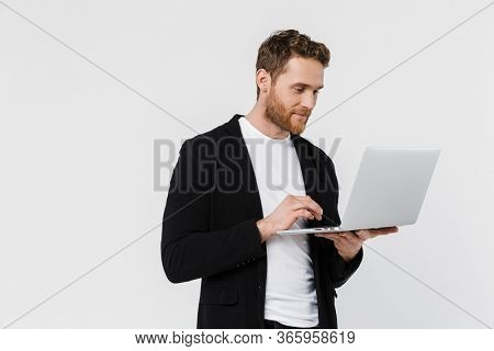 Image of handsome pleased man in jacket smiling and using laptop isolated over white background