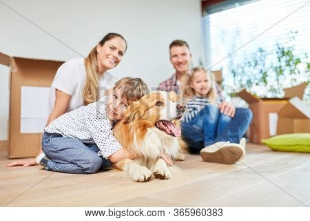 Family with children and dog happily sitting in new home as a home