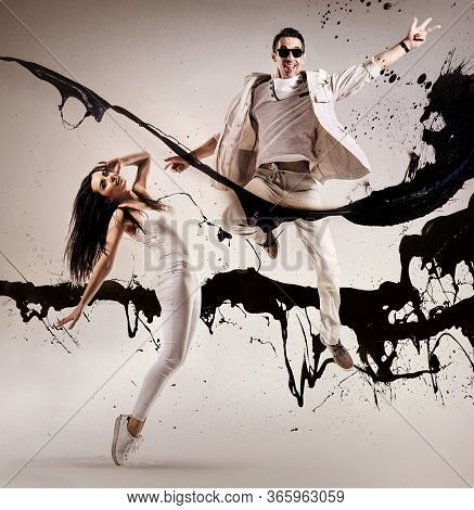 Full length profile shot of a young woman and a guy performing a dance jump