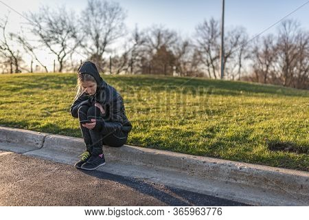 Portrait Of A Girl, Sitting On A Curb, Looking At Her Smartphone