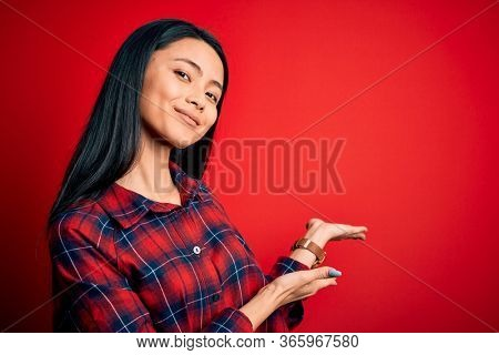 Young beautiful chinese woman wearing casual shirt over isolated red background Inviting to enter smiling natural with open hand