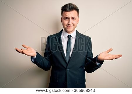 Young handsome business man wearing elegant suit and tie over isolated background clueless and confused with open arms, no idea concept.