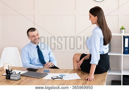 Lustful Boss Flirting With Secretary Girl Sitting At Workplace In Office. Flirt And Work Relationshi