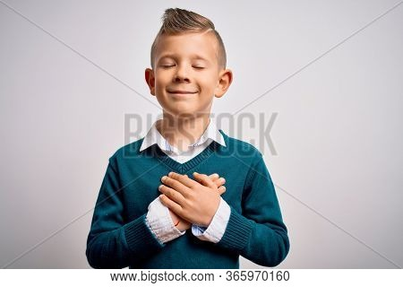 Young little caucasian kid with blue eyes standing wearing elegant clothes over isolated background smiling with hands on chest with closed eyes and grateful gesture on face. Health concept.