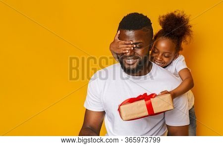 Surprise For Father. Cheerful Girl Congratulating Her Daddy, Closing His Eyes With Gift Box, Orange