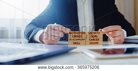 Personal Development Concept. A Man Lays On The Table Wooden Blocks With The Words Motivation, Growt