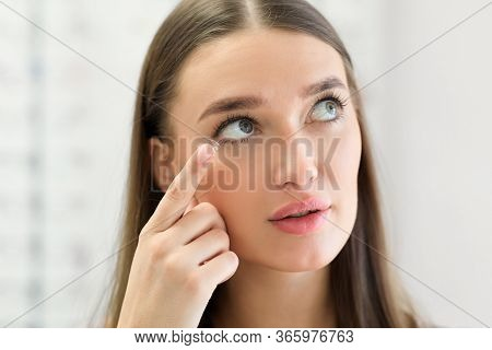 Contact Lens For Vision Concept. Close Up Portrait Of Young Woman Applying Eye Lens And Looking Up