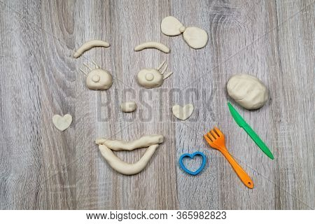 Children Sculpt From Salt Dough, Clay, Plasticine On A Wooden Background. Childrens Creativity. Manu