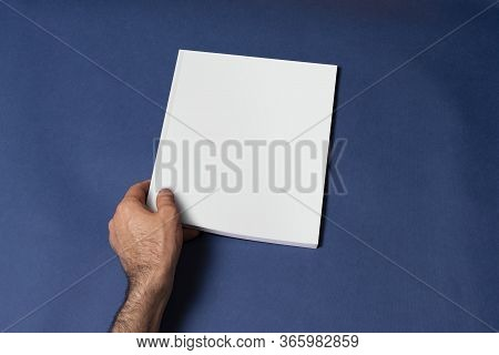 Male Hand Holding A Closed Book-catalog With Blank Cover On Blue Background, Mock-up Series Template
