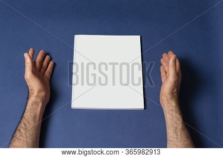 Male Hands Around A Closed Book-catalog With Blank Cover On Blue Background, Mock-up Series Template