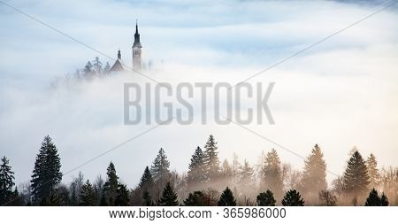 amazing panorama of Lake Bled Blejsko Jezero on a foggy morning with the Pilgrimage Church of the Assumption of Maria on a small island and Bled Castle and Julian Alps in backgroud