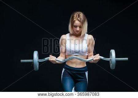 Close-up Portrait Of A Fitness Muscular Young Girl Posing With Curly Barbell At The Gym Isolated On
