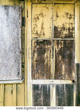 Weathered Wooden Door On Wall Of Abandoned Building With Peeling Old Paint
