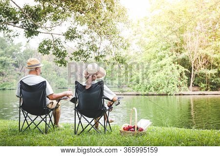 Elderly Couple Sitting On A Black Chair In A Shady Garden And There Is A Picnic Basket For Bread And