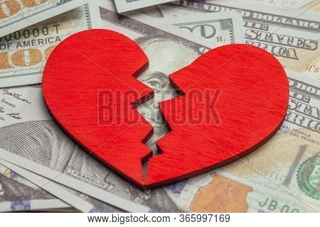Broken Heart Because Of Money. Heart On A Stack Of Cash Dollars. Crack In The Red Heart, Breaking Th