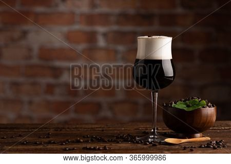 Irish Coffee With Whiskey. Alcoholic Warming Cocktail With Foam From Cream And Coffee Beans On It.